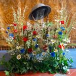Poppies and cornflowers with a WW1 helment and rosemary to symbolise rememberance