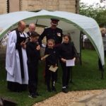vicar and children under an canopy