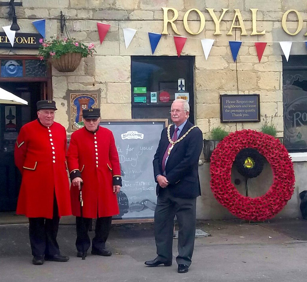 Wreath of poppies, chelsea pensioners in red coats and the Mayor of Cheltenham.